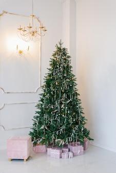 Eleganter und schöner weihnachtsbaum im inneren eines hellen wohnzimmers.