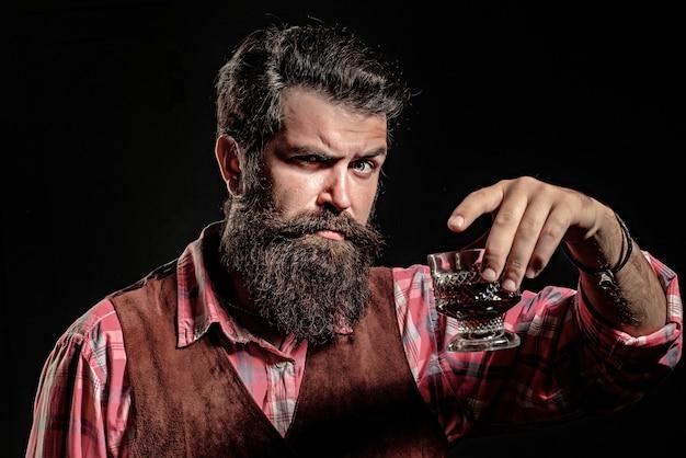 Eleganter und stilvoller mann in klassischer kleidung, der glas mit whisky in der hand hält