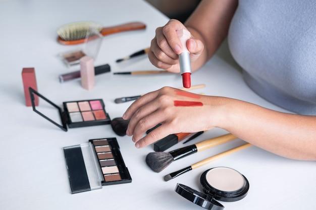 Eleganter weiblicher schönheitsblogger, der prüfungsschönheitskosmetik unter verwendung der produktmake-up-tutorenkosmetik und des verkaufsprodukts zeigt