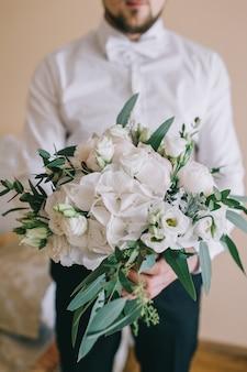 Eleganter zarter strauß der braut aus weißen pfingstrosen, hortensien, rosen und einem grünen zweig in den händen des bräutigams im raum.
