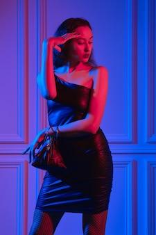 Elegantes afroamerikanisches model posiert mit dreieckiger handtasche unter neonlichtern