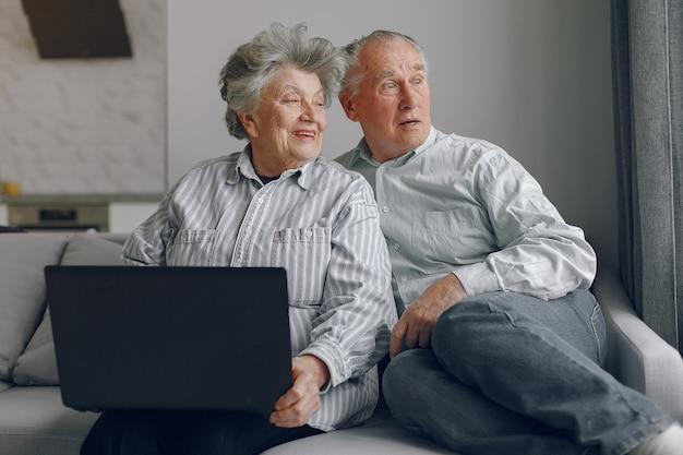 Elegantes altes ehepaar, das zu hause sitzt und einen laptop benutzt