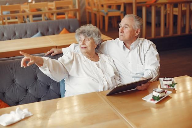 Elegantes altes ehepaar in einem café mit einer tablette