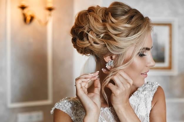 Elegantes blondes modellmädchen mit stilvoller hochzeitsfrisur, im weißen spitzenkleid setzt ihren ohrring auf und posiert im innenraum, hochzeitsvorbereitung der jungen braut