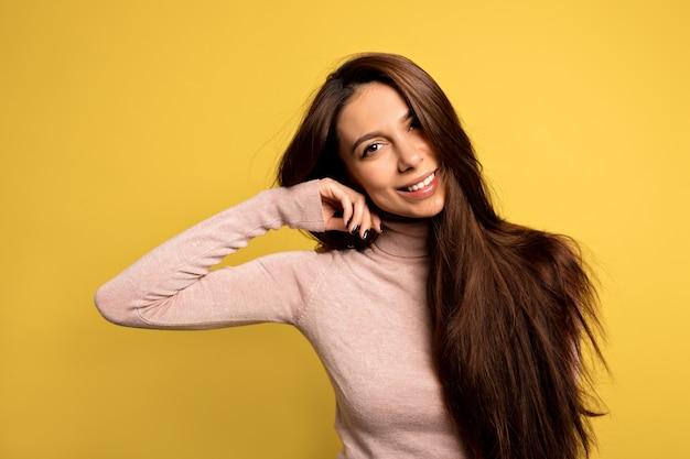 Elegantes europäisches mädchen mit schönen braunen augen, die kinn mit den fingern berühren und sanft lächeln. nahaufnahmeporträt der trendigen jungen frau, die im gelben raum aufwirft