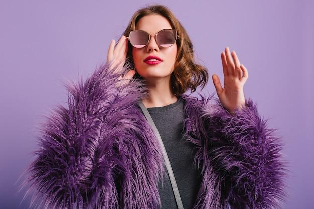 Elegantes europäisches weibliches modell, das auf lila hintergrund mit erfreutem lächeln aufwirft
