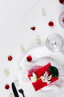 Elegantes feiertagsgedeck mit rotem bandgeschenk