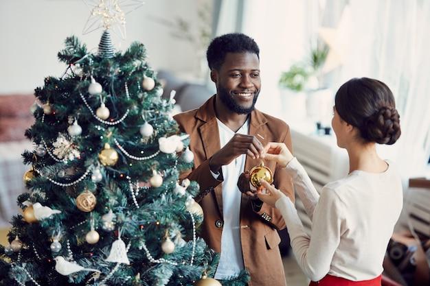 Elegantes gemischtes paar, das weihnachtsbaum verziert