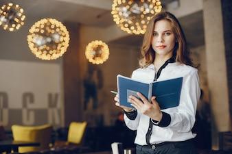 Elegantes Geschäftsmädchen mit Notizbuch