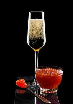 Elegantes glas gelber champagner mit rotem kaviar auf goldenem löffel und glasbehälter kaviar auf marmorbrett auf schwarz.