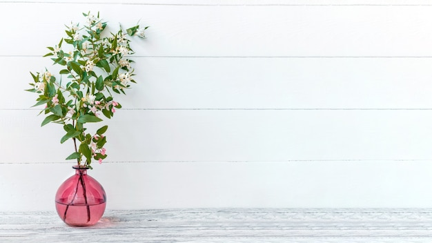 Elegantes hausfrühlingsblumendekor, zweigblumenstrauß. blühende frühlingszweige von blumen in rosa glasvase auf weißem hintergrund der hölzernen weinlese. langes webbanner mit kopienraum.