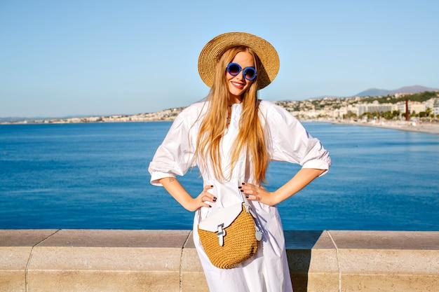 Elegantes hübsches blondes modell, das am standpunkt von nizza frankreich aufwirft und stilvolles sommeroutfit trägt
