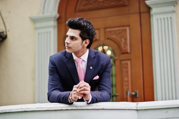 Elegantes indisches machomannmodell auf anzug und rosa bindung lehnte sich auf dem geländer.