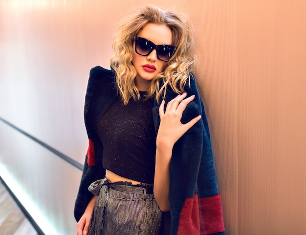 Elegantes innenporträt des jungen blonden sexy modells, das nahe ziegelmauer aufwirft, die trendigen hellen pelzmantel trägt