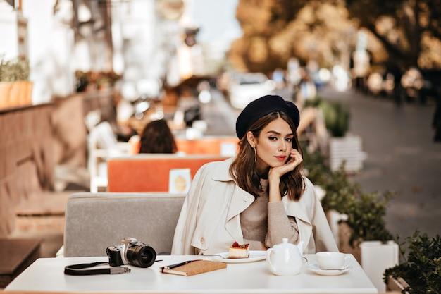 Elegantes junges mädchen mit brünetter welliger frisur, vintage-barett, beigefarbenem trenchcoat beim mittagessen auf der café-terrasse in der warmen, sonnigen herbststadt
