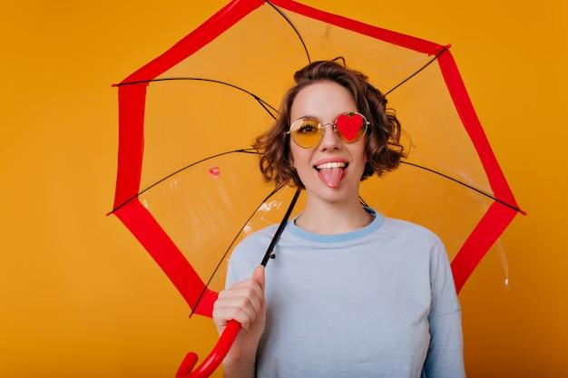 Elegantes junges weibliches modell, das mit herausgestellter zunge aufstellt und unter sonnenschirm steht. lustiges lockiges mädchen, das regenschirm auf orange wand hält.