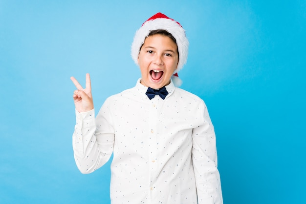 Elegantes kind, das einen sankt-hut an einem weihnachtstag trägt