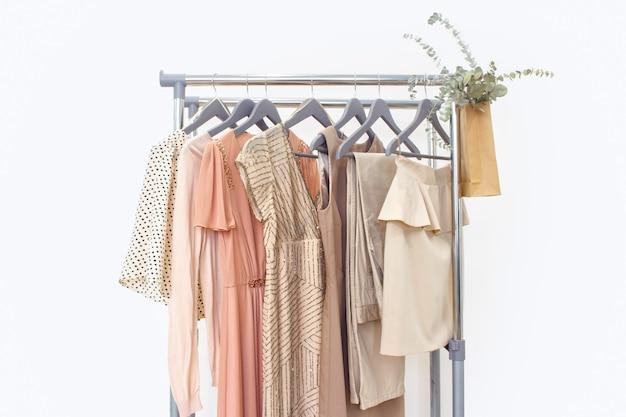 Elegantes kleid, pullover, hose und andere mode-outfit pastellbeige farbe. frühjahrsputz nach hause kleiderschrank.
