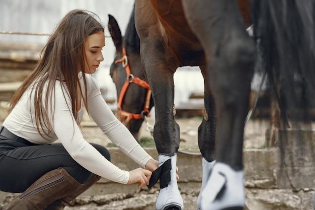 Elegantes mädchen in einem bauernhof mit einem pferd