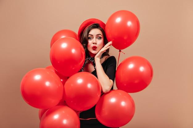 Elegantes mädchen in roter baskenmütze und schwarzem kleid bläst kuss und hält riesige luftballons.