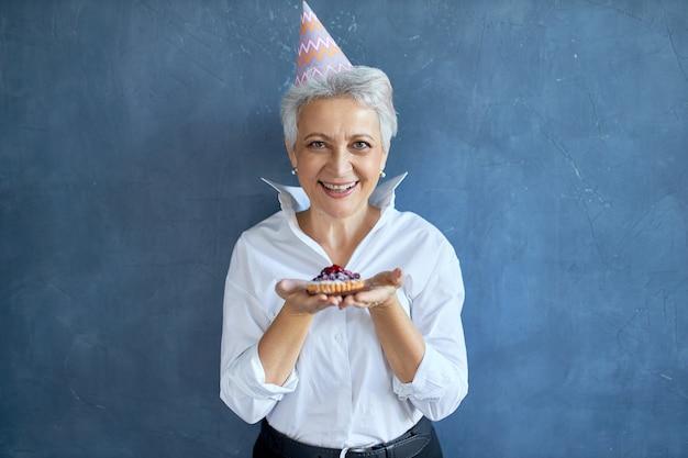 Elegantes mittleres alter im weißen hemd, das jubiläum feiert, das lokal mit frisch gebackenem kuchen posiert, freudigen gesichtsausdruck habend