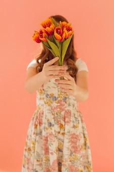 Elegantes modell, das tulpenblumen hält