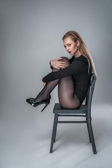Elegantes modell in body und strumpfhose posiert auf einem stuhl
