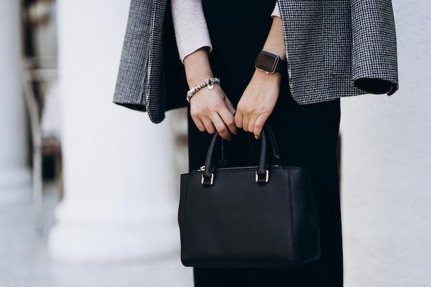 Elegantes outfit. nahaufnahme der strukturierten großen dunklen tasche. model posiert auf der straße, trägt kurze hosen, einen cremigen pullover, einen grauen mantel oder eine graue jacke und weiße turnschuhe. weibliches modekonzept.
