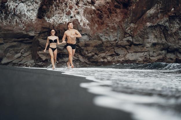 Elegantes paar an einem strand in der nähe von felsen