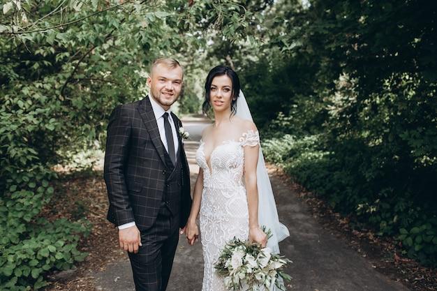 Elegantes paar, das bei sonnenuntergang, liebesgeschichte, porträt von braut und bräutigam am hochzeitstag geht