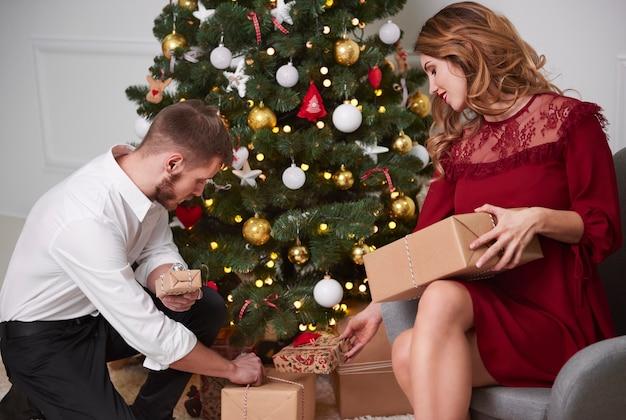 Elegantes paar, das geschenke unter weihnachtsbaum setzt