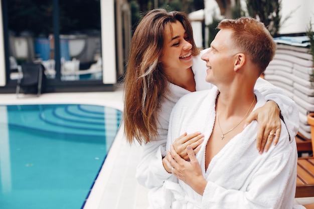 Elegantes paar, das nahe einem schwimmbad sitzt