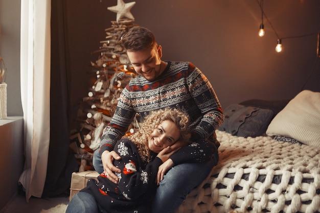 Elegantes paar, das zu hause nahe weihnachtsbaum sitzt