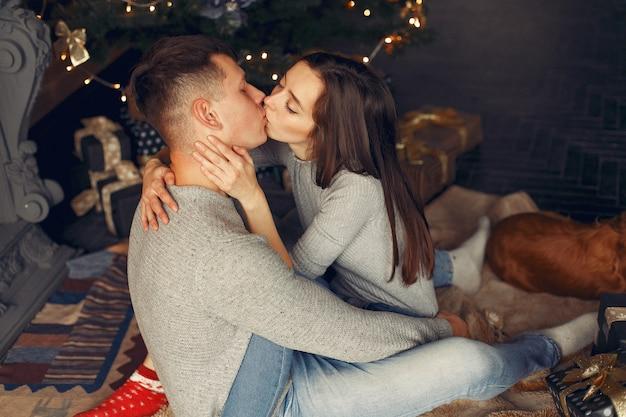 Elegantes paar zu hause in der nähe von weihnachtsbaum