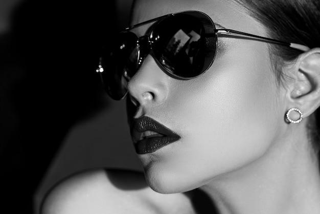 Elegantes schickes weibliches modell in der modischen sonnenbrille mit den roten lippen. porträt einer ernsten frau im dunkeln