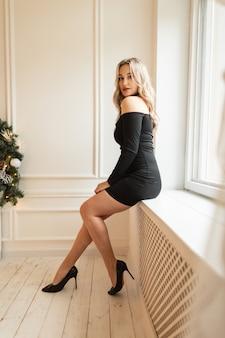 Elegantes schönes mädchen im modischen schwarzen kleid mit sexy beinen und schuhen sitzt in der nähe von fenstern