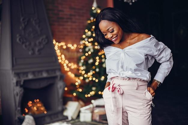 Elegantes schwarzes mädchen in den weihnachtsdekorationen
