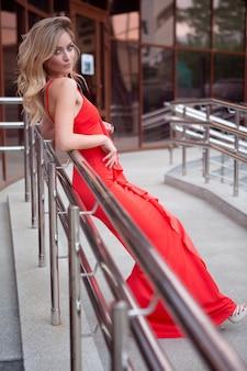 Elegantes sexy blauäugiges mädchen in einem abendlichen roten kleid, das auf dem geländer der straßentreppe lehnt
