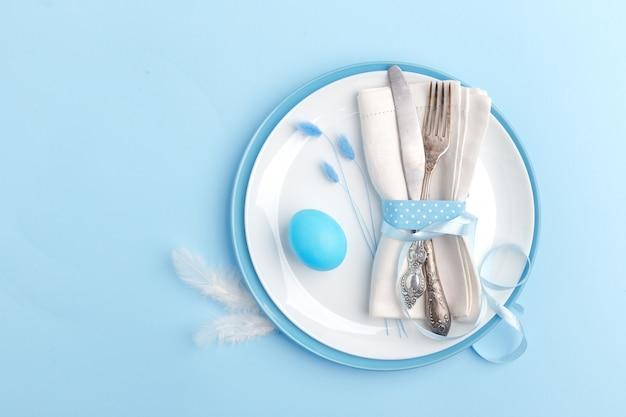 Elegantes stilvolles gedeck. messer und gabel auf einer serviette auf einer platte auf einer blauen oberfläche.