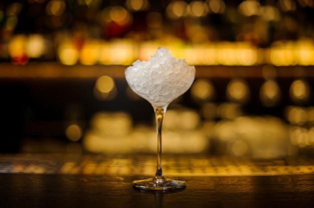 Elegantes transparentes cocktailglas mit eiswürfeln auf der bartheke des pubs vor dem unscharfen hintergrund der lichter