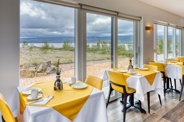 Elegantes und minimalistisches restaurant in einem skandinavischen hotel mit fantastischem blick auf die landschaft und die berge