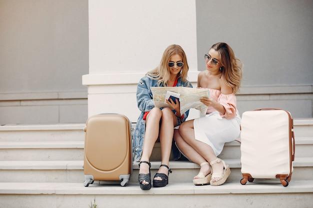 Elegantes und stilvolles mädchen, das mit einem koffer sitzt