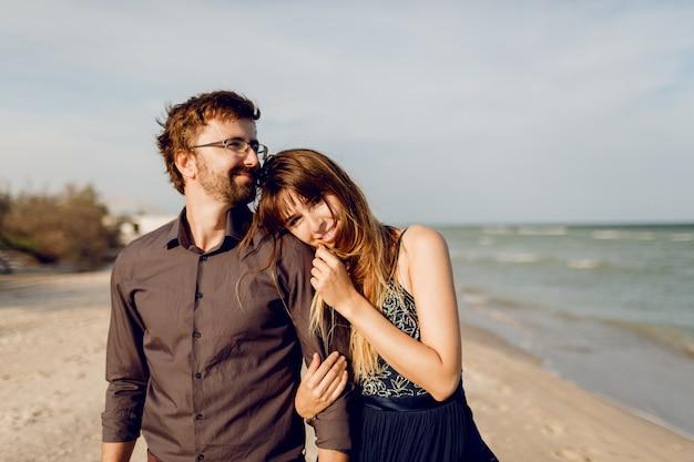 Elegantes verliebtes paar, das am sonnigen abendstrand geht, glückliche frau, die ihren ehemann in verlegenheit bringt.