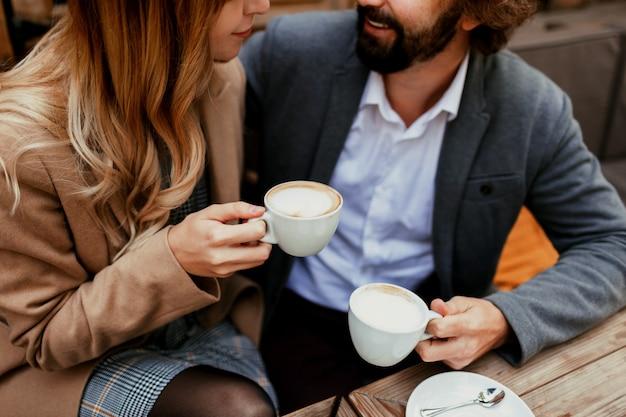 Elegantes verliebtes paar, das in einem café sitzt, kaffee trinkt, sich unterhält und die zeit miteinander genießt. selektiver fokus auf tasse.