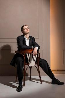 Elegantes weibliches modell, das im studio auf einem stuhl im jackenanzug sitzend aufwirft. neues weiblichkeitskonzept