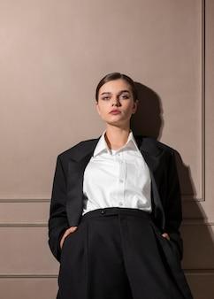 Elegantes weibliches modell, das im studio im jackenanzug aufwirft. neues weiblichkeitskonzept