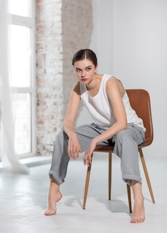 Elegantes weibliches modell, das im trägershirt und in der grauen hose in einem hellen studio aufwirft. neues weiblichkeitskonzept