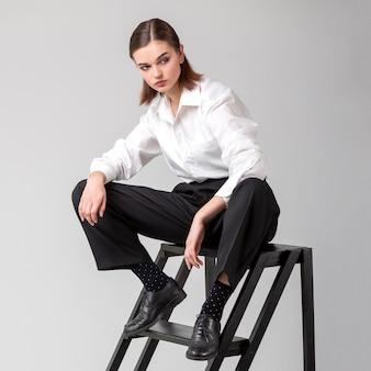 Elegantes weibliches modell, das in der treppe in einem jackenanzug aufwirft. neues weiblichkeitskonzept