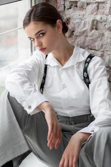 Elegantes weibliches modell, das in einem fenster im eleganten weißen hemd und in den hosenträgern aufwirft. neues weiblichkeitskonzept