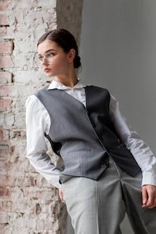 Elegantes weibliches modell, das in einem fenster in der eleganten weste aufwirft. neues weiblichkeitskonzept